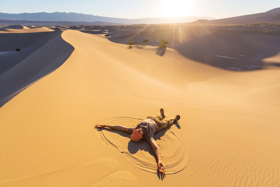 death valley national park in california man lying on sand enjoying the sun im december