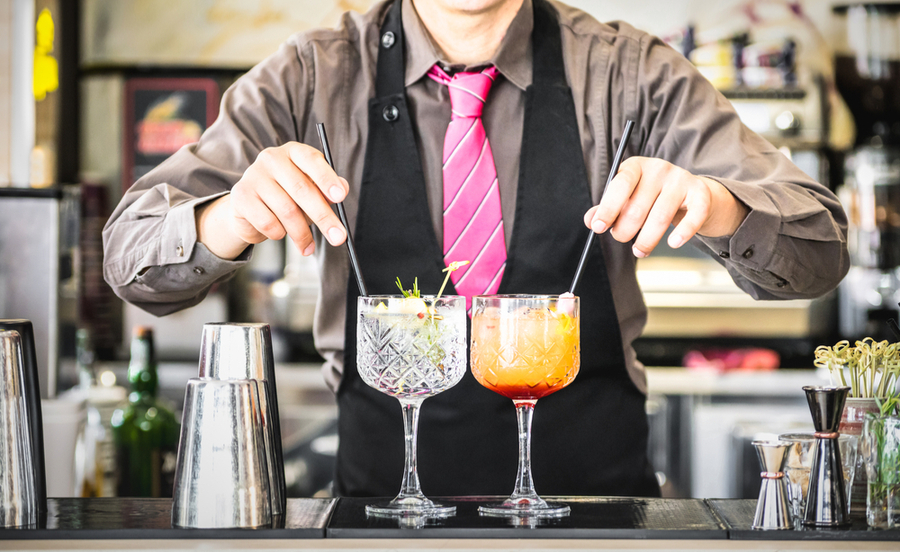 bartender serving gin tonic and tequila sunrise in california bar